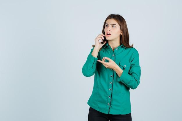 Junges mädchen, das mit telefon spricht, mit zeigefinger in grüner bluse, schwarzer hose nach links zeigt und überrascht aussieht. vorderansicht.