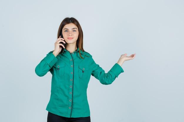 Junges mädchen, das mit telefon spricht, palme beiseite in grüner bluse, schwarze hose und fröhlich aussehend, vorderansicht ausbreitet.