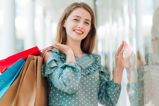 Junges mädchen, das mittleren schuss der einkaufstaschen hält