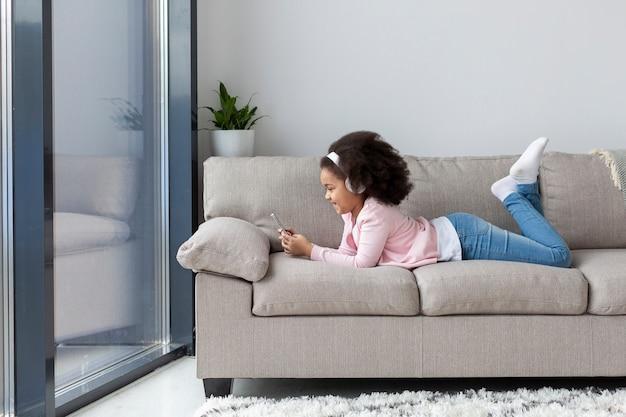 Junges mädchen, das musik auf der couch hört
