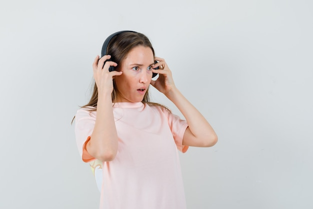 Junges mädchen, das musik mit kopfhörern im rosa t-shirt genießt und erstaunt, vorderansicht schaut.