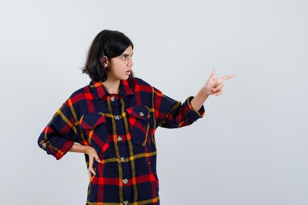 Junges mädchen, das nach rechts zeigt, während es die hand in kariertem hemd an der taille hält und neugierig aussieht. vorderansicht.