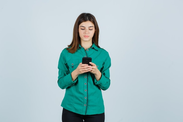 Junges mädchen, das nachrichten am telefon in der grünen bluse, in der schwarzen hose schreibt und konzentriert schaut. vorderansicht.