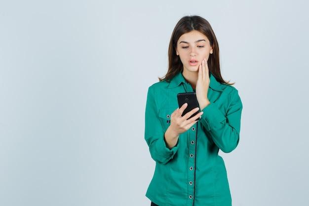 Junges mädchen, das nachrichten am telefon liest, hand auf wange in grüner bluse, schwarzer hose hält und fokussiert, vorderansicht schaut.