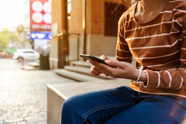 Junges mädchen, das neue app-technologie des telefons in der stadt hält.