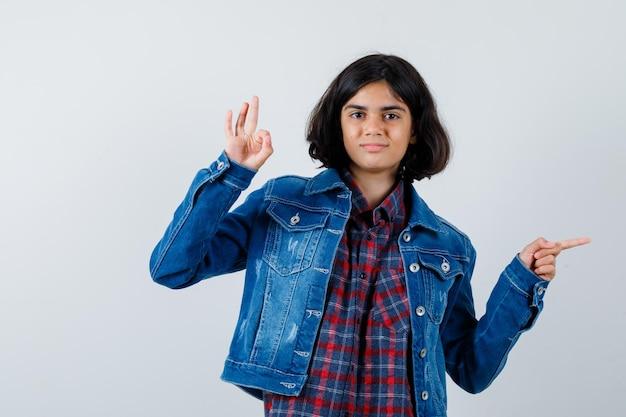 Junges mädchen, das ok-zeichen zeigt und in kariertem hemd und jeansjacke nach rechts zeigt und glücklich aussieht. vorderansicht.