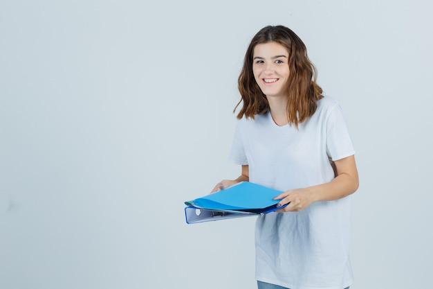 Junges mädchen, das ordner im weißen t-shirt hält und glücklich schaut. vorderansicht.