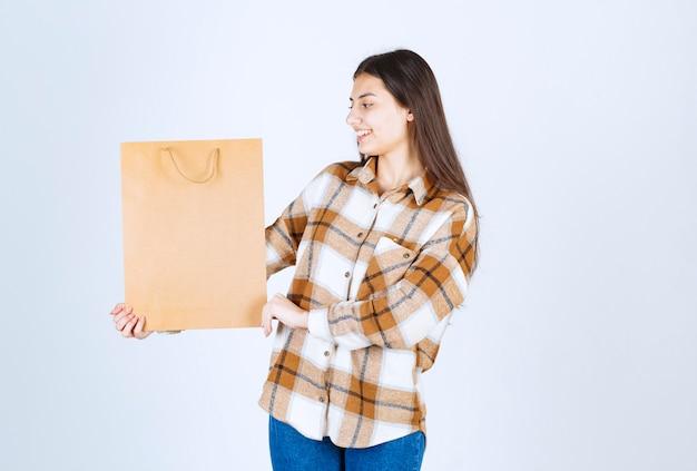 Junges mädchen, das papierhandwerkpaket hält und über weißer wand steht.