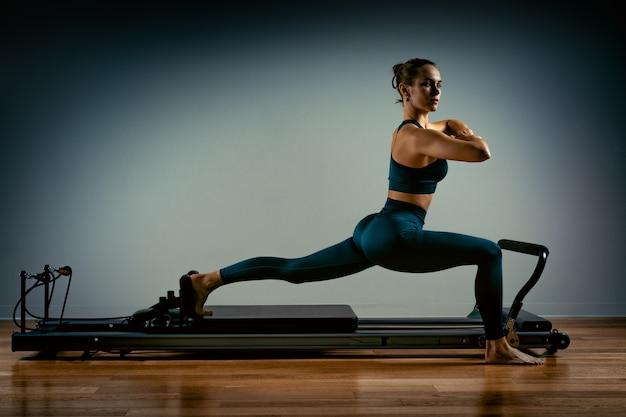 Junges mädchen, das pilates-übungen mit einem reformerbett macht. schöner schlanker fitnesstrainer auf grauem hintergrund des reformators, zurückhaltend, kunstlicht. fitness-konzept