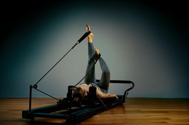 Junges mädchen, das pilates-übungen mit einem reformerbett macht. schöner schlanker fitnesstrainer auf reformer