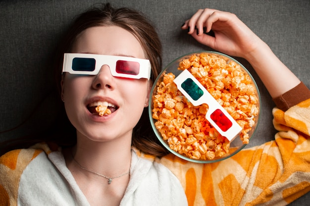 Junges mädchen, das popcorn in den 3d-gläsern isst