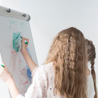 Junges mädchen, das recyclingschild auf whiteboard zeichnet