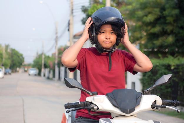 Junges mädchen, das seinen motorradhelm in der stadtstraße befestigt