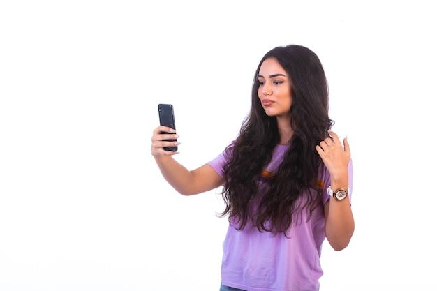 Junges mädchen, das selfie mit ihrem handy nimmt