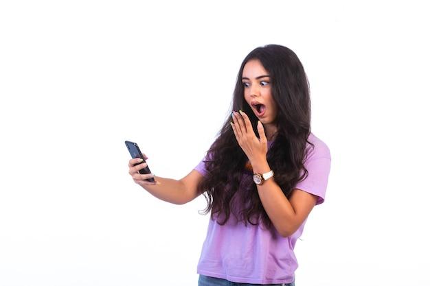 Junges mädchen, das selfie nimmt oder einen videoanruf macht und überrascht wird.