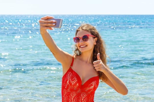 Junges mädchen, das spaß hat, smartphone selfie fotos von zu machen. reiseurlaub. glückliche junge frau, die handzeichendaumen oben auf strand gibt