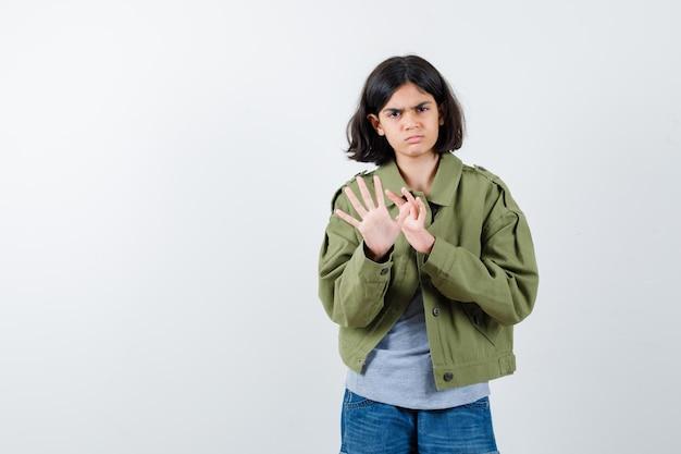 Junges mädchen, das stoppschild in grauem pullover, khakijacke, jeanshose zeigt und wütend aussieht. vorderansicht.