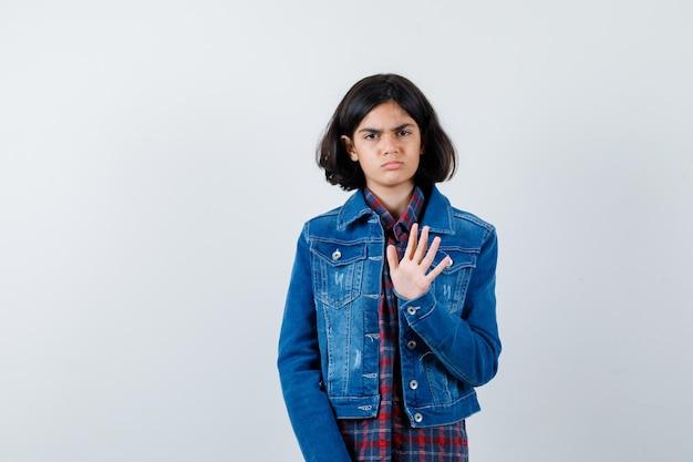 Junges mädchen, das stoppschild in kariertem hemd und jeansjacke zeigt und ernst aussieht. vorderansicht.