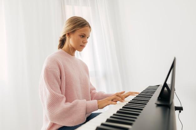 Junges mädchen, das tastaturinstrument zu hause spielt