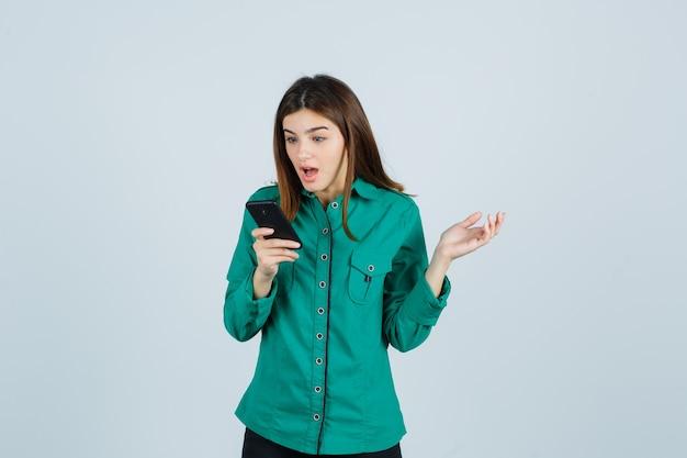Junges mädchen, das telefon betrachtet, hand in der überraschten weise in der grünen bluse, in der schwarzen hose streckt und schockiert schaut, vorderansicht.