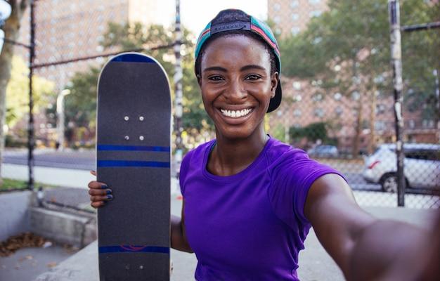 Junges mädchen, das tricks mit dem skateboard in einem skatepark durchführt