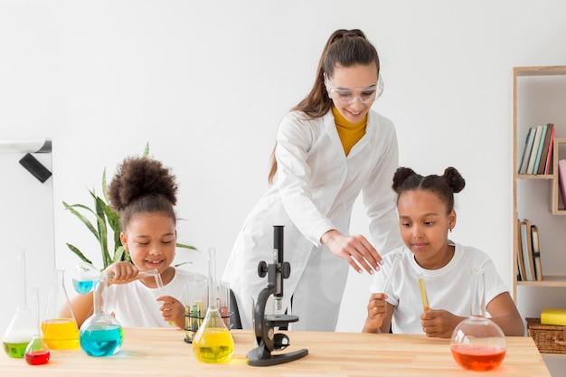 Junges mädchen, das über chemie von wissenschaftlerin lernt