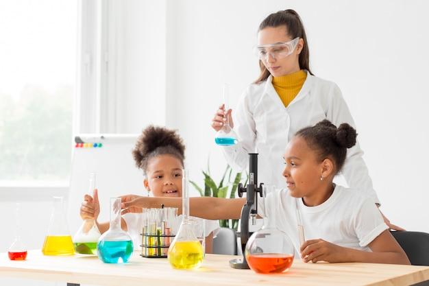 Junges mädchen, das über wissenschaft von wissenschaftlerin lernt