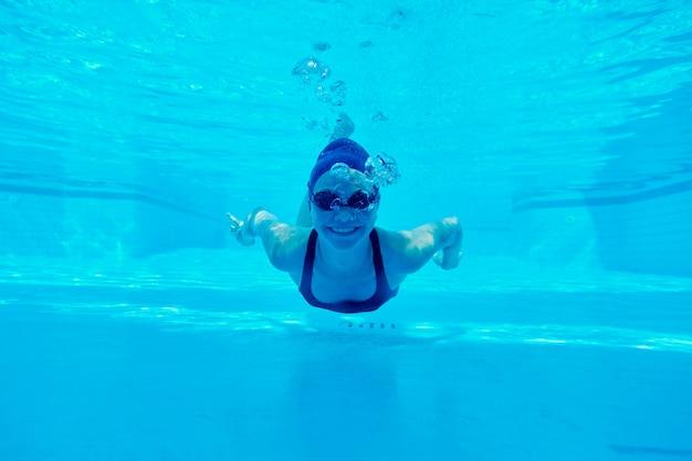 Junges mädchen, das unter wasser im pool schwimmt, weiblich schaut und lächelt