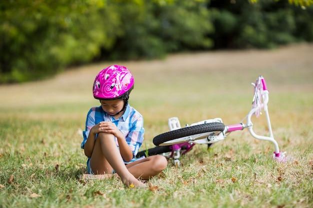 Junges mädchen, das verletzt erhält, nachdem es vom fahrrad gefallen ist