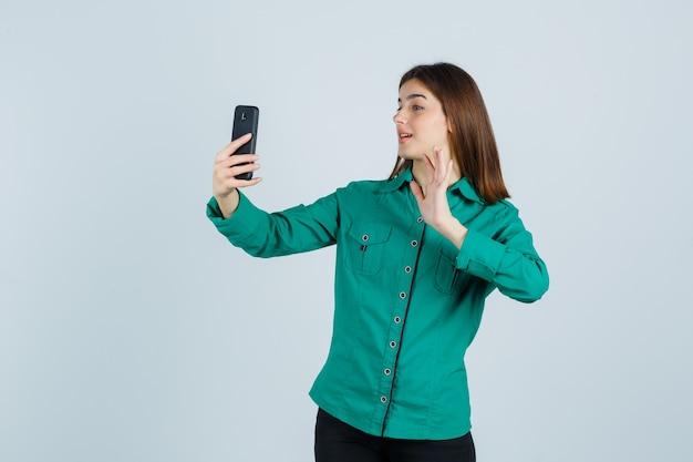 Junges mädchen, das videoanruf macht, hand winkt, um hallo in grüner bluse, schwarzer hose zu sagen und glücklich zu schauen, vorderansicht.