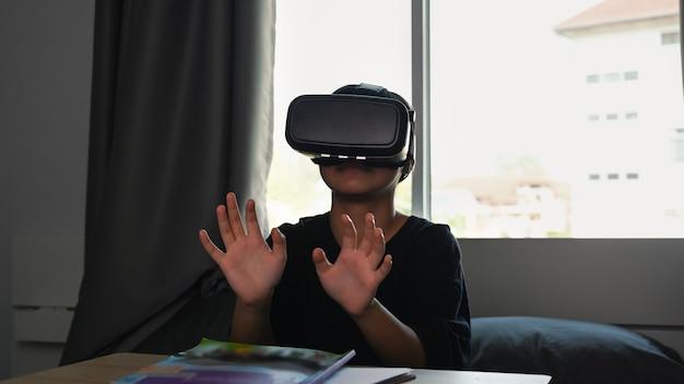 Junges mädchen, das videospiele mit virtual-reality-headset spielt und versucht, etwas mit der hand zu berühren, während es zu hause auf dem bett sitzt.