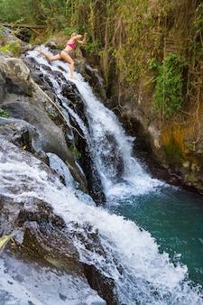 Junges mädchen, das vom hohen felsen zum natürlichen wasserbecken unter wasserfall in den tropischen bergen springt