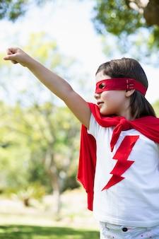 Junges mädchen, das vortäuscht, ein superheld zu sein