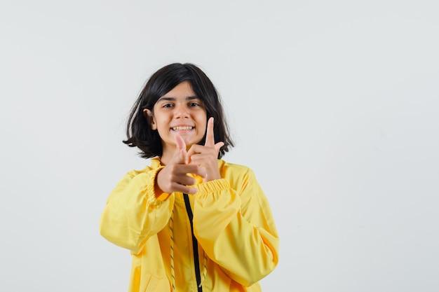 Junges mädchen, das waffengesten mit beiden händen in der gelben bomberjacke zeigt und glücklich schaut.
