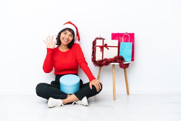 Junges mädchen, das weihnachten auf dem boden sitzt, isoliert auf weißem hintergrund, der mit den fingern fünf zählt