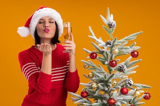 Junges mädchen, das weihnachtsmütze trägt, die nahe verziertem weihnachtsbaum steht, der glas champagner hält, der schlagkuss mit geschlossenen augen, die auf orange wand lokalisiert sind