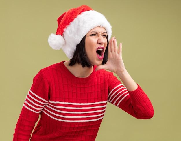 Junges mädchen, das weihnachtsmütze trägt, die seite hält, die hand nahe mund hält, der laut zu jemandem ruft, der auf olivgrünem hintergrund isoliert wird
