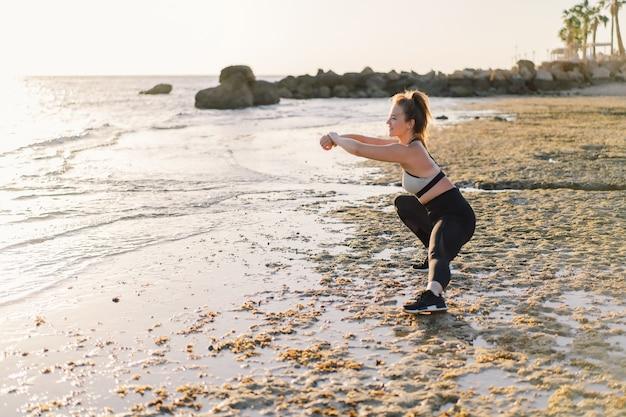 Junges mädchen, das yoga-fitnessübung im freien im schönen meer und im morgensonnenaufgang tut. lebensstil. gesundes und fitness-konzept