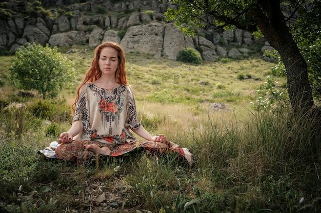 Junges mädchen, das yoga im park tut. ruhe und meditation. junges rothaariges mädchen unter einem baum entspannt sich