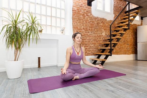 Junges mädchen, das yoga in der meditationshaltung praktiziert. sie entspannt sich zu hause. platz für text.