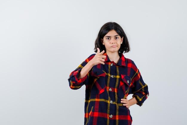 Junges mädchen, das zeigt, während es die hand auf der taille im karierten hemd hält und süß aussieht, vorderansicht.