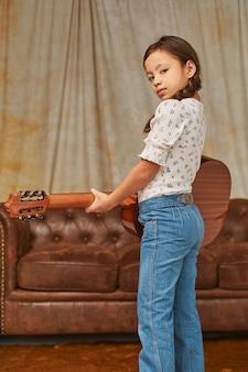 Junges mädchen, das zu hause gitarre spielt