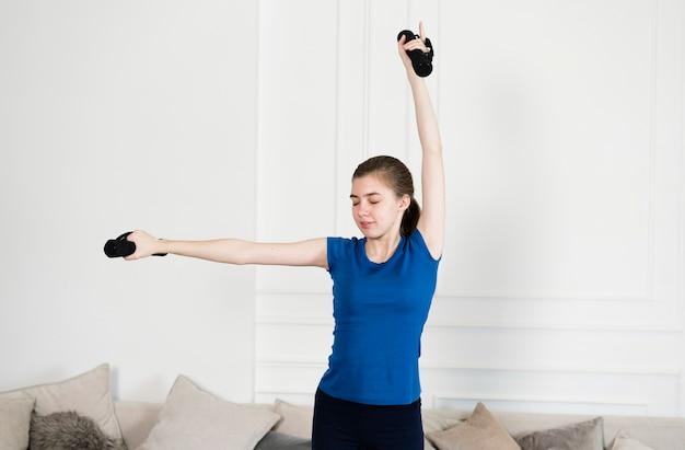Junges mädchen, das zu hause mit gewichten trainiert