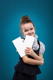 Junges mädchen, das zwei papiere und das lächeln hält