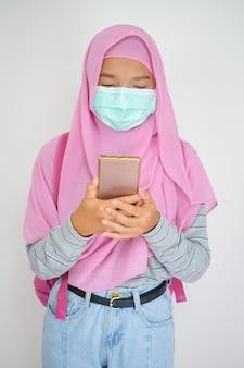 Junges mädchen der studentin trägt eine maske und benutzt ein handy auf weißem hintergrund ein muslimisches mädchen