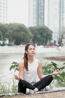 Junges mädchen der vorderansicht, das yoga tut