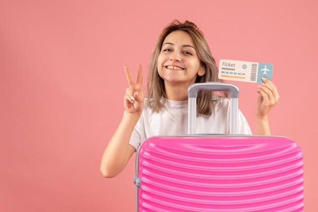 Junges mädchen der vorderansicht mit rosa koffer, das ticket hält, das siegeszeichen gestikuliert
