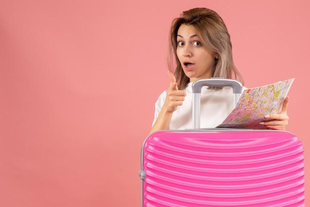 Junges mädchen der vorderansicht mit rosa koffer, der karte hält, die mit dem finger nach vorne zeigt