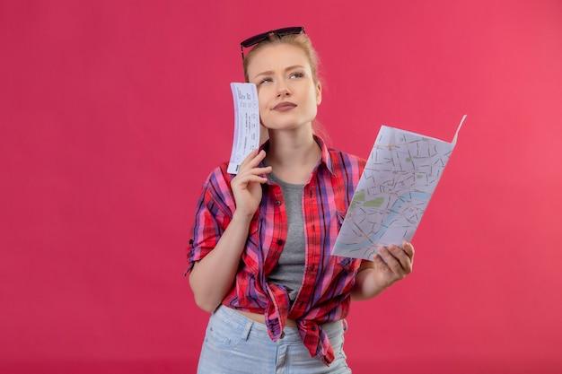 Junges mädchen des denkenden reisenden, das rotes hemd und brille auf ihrem kopf hält karte mit ticket auf lokalisiertem rosa hintergrund trägt