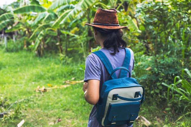 Junges mädchen des hippies mit rucksack sonnenuntergang genießend